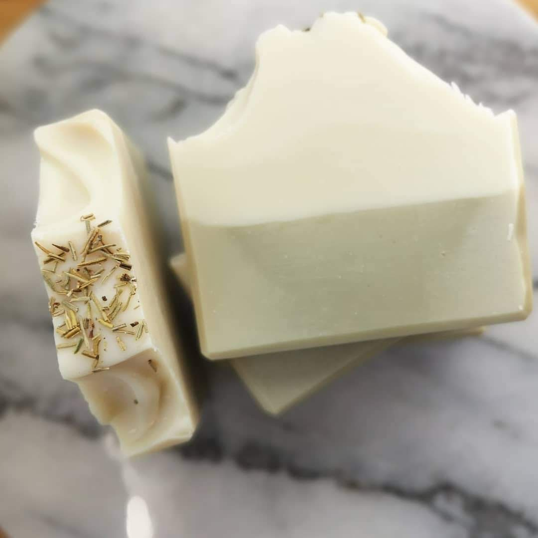 Layered rosemary soaps on marble. Soaps are white on top and green on the bottom.
