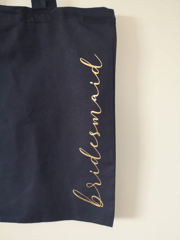 the word bridesmaid in gold lettering on navy tote bag