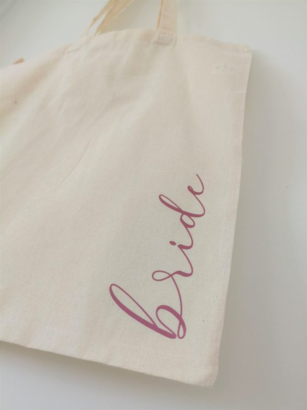 the word bride in pink lettering on natural tote bag
