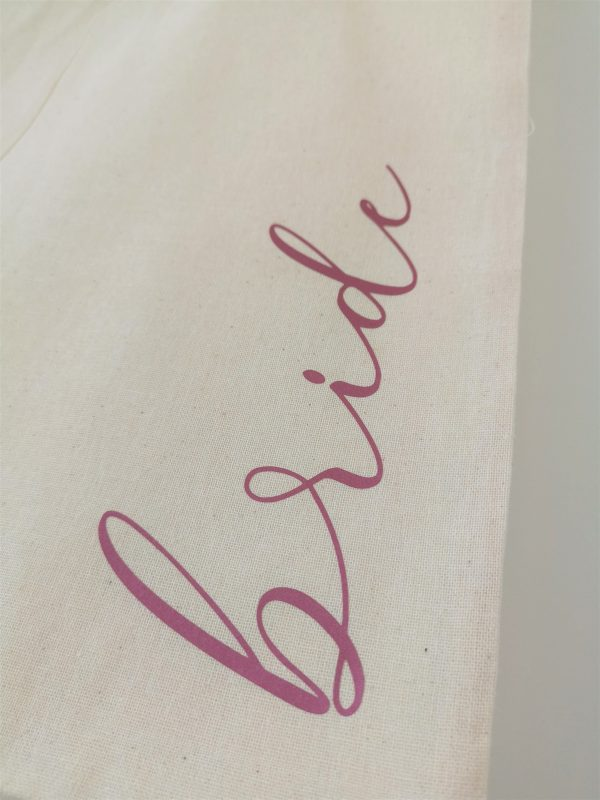 Close up of the word bride in pink lettering on natural tote bag