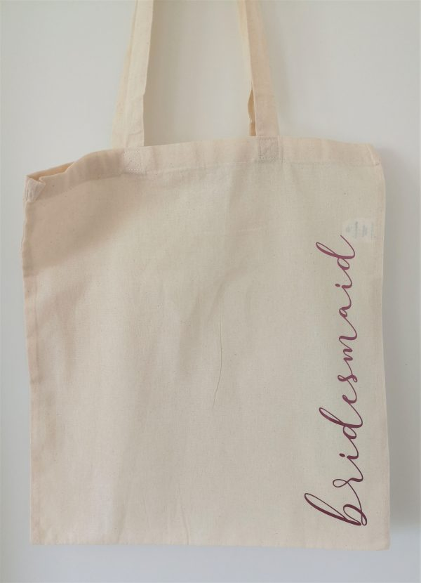 Natural coloured tote bag with the word bridesmaid in pink lettering