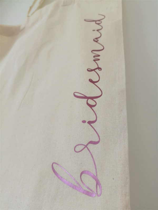 Close up of the word bridesmaid in pink lettering on natural tote bag