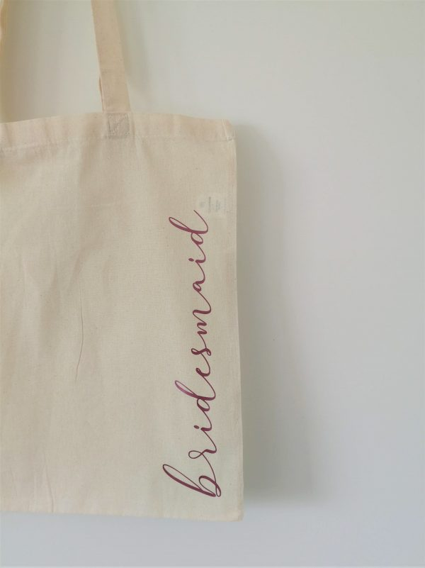 the word bridesmaid in pink lettering on natural tote bag